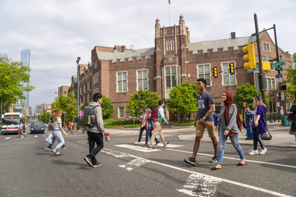 Penn students crossing busy street intersection